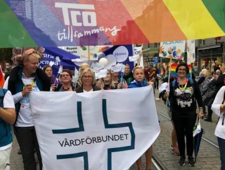 Vårdförbundet går i parad med en Vårdförbundet-flagga och en regnbågsfärgad banderoll med text