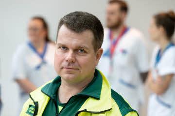En manlig ambulansförare tittar in i kameran med allvarlig min