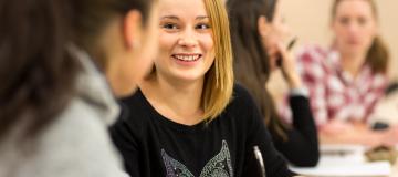 Kvinnliga unga studenter, civilklädda, sitter ner vid skolbänkar med penna och papper och samtalar med varandra