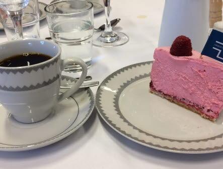 En kaffekopp med kaffe i samt en tallrik med en bit tårta med hallon och en liten flagga i med Vårdförbundets logga