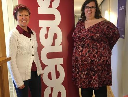 Två kvinnor står på vars en sida om en rollup som det står Sensus på.
