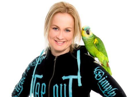 En ljushårig kvinna i svart hoodtröja med en papegoja på sin axel.