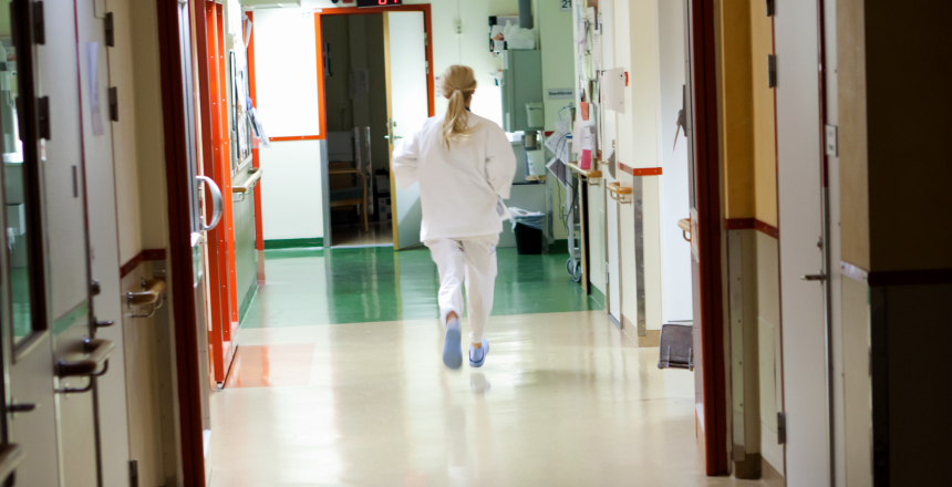 Rygg på ensam sjuksköterska som går i en sjukhuskorridor