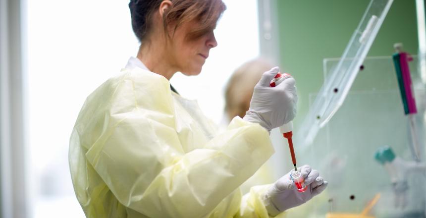 Kvinna i gul skyddsklädsel analyserar ett blodprov