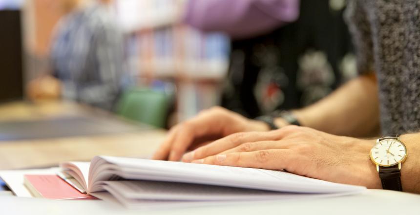En students händer i en bok på biblioteket