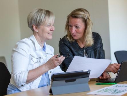 Två kvinnor en med kort hår och en med mellanlångt hår sitter vid ett bord och samtalar. Framför sig har dom vars en dator. En utav kvinnorna har ett papper i handen.