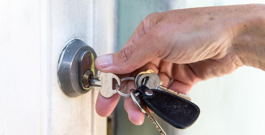 Ett lås med nyckel i där en hand vrider om nyckeln