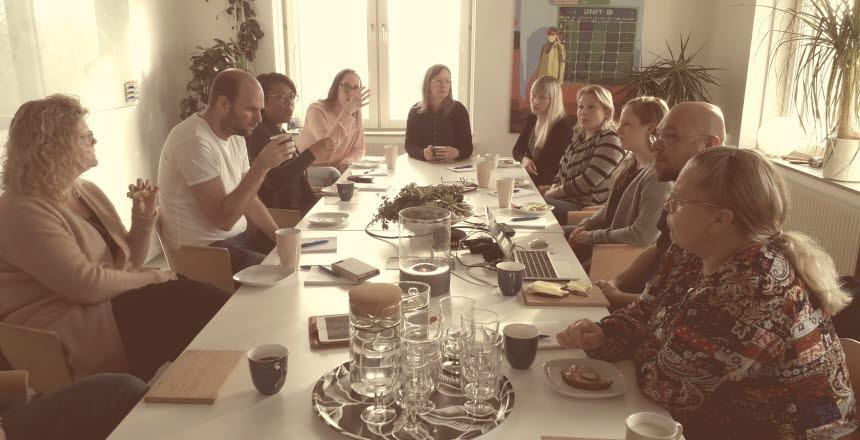 Ett tiotal personer som sitter kring ett konferensbord och samtalar och fikar