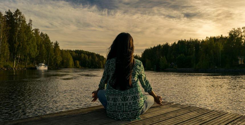 Kvinna sitter på en brygga med ryggen oemot vid vattnet