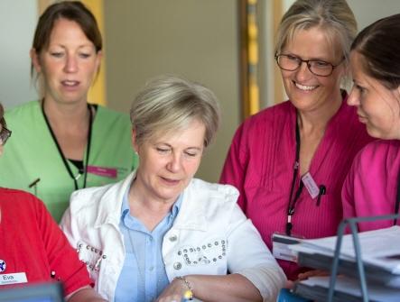 Fem sjukvårdsklädda kvinnor som står tillsammans och tittar på någonting och samtalar