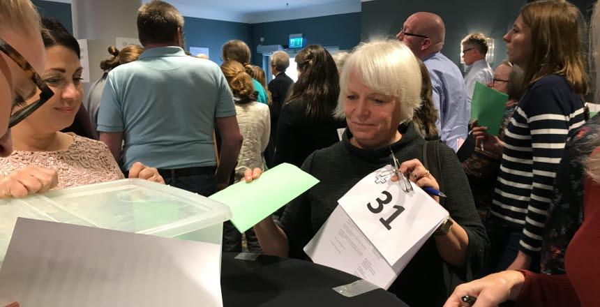 En kvinna lägger en röstsedel i en låda