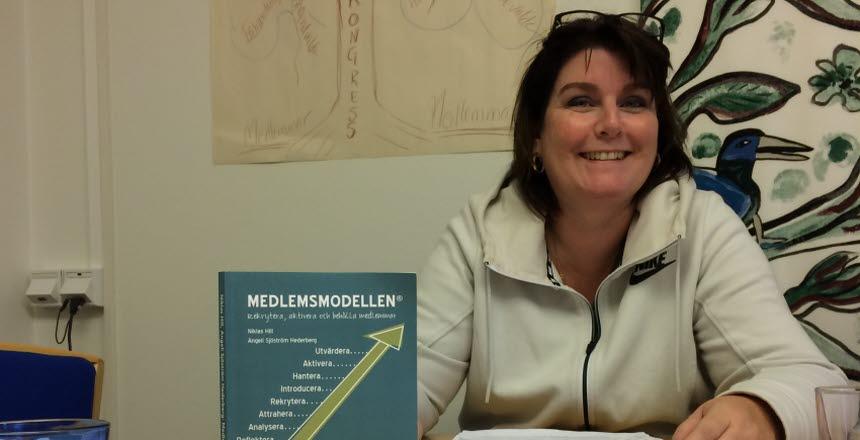 En kvinna sitter vid ett konferensbord med papper på bordet och en bok med titeln Medlemsmodellen på.