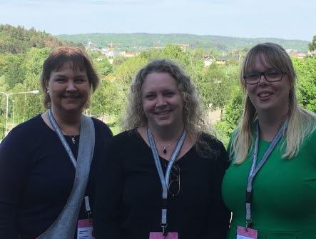 Tre kvinnor som står bredvid varandra med fin utsikt med grönska bakom sig.
