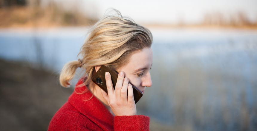 Kvinna håller mobiltelefon till örat.