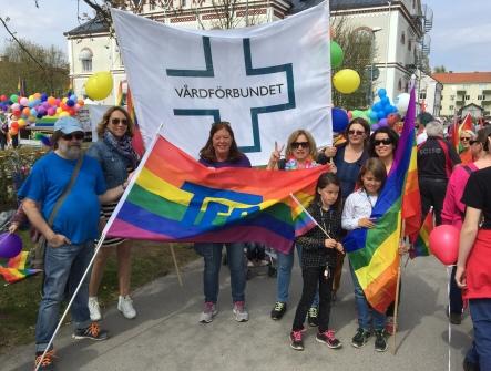 Bild från Pride paraden i Växjö människor som håller Vårdförbundets banderoll samt en Prideflagga från TCO