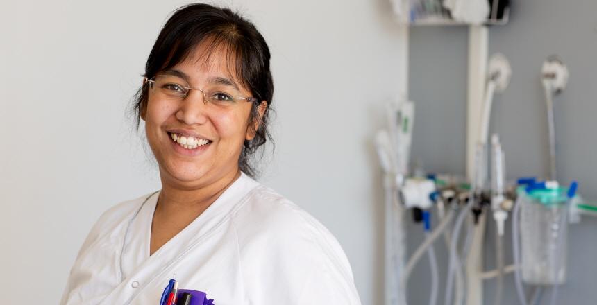 Glad specialistsjuksköterska i ett behandlingsrum.