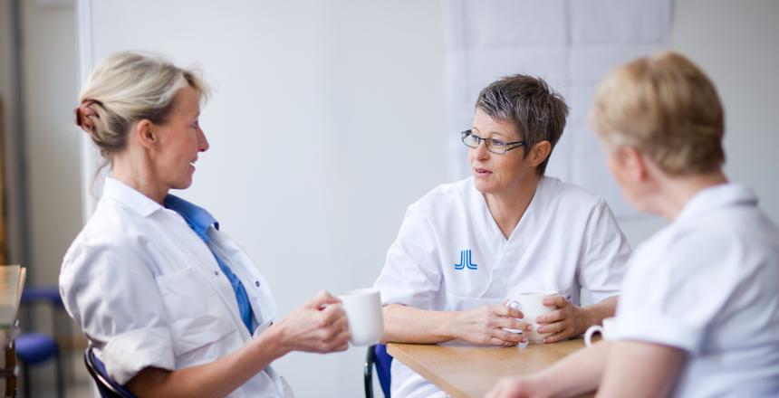 Tre kvinnor som är sjukvårdsklädda sitter och samtalar och dricker kaffe runt ett bord.
