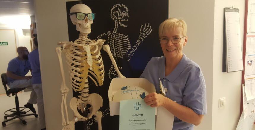 Karin Larsson Bylund, dagens röntgensjuksköterska, i händerna har hon en tårta i kartong och ett diplom. Bredvid henne står ett skelett med glasögon på sig.