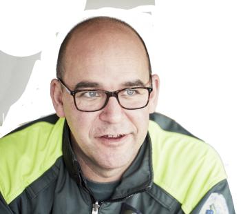 Manlig ambulanssjuksköterska med glasögon ler