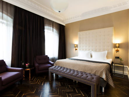 Hotellrum med en dubbelsäng, tvår lampor på väggen som lyser och två fotöljer vid sidan om sängen.