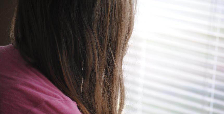Kvinna eller flicka tittar ut genom ett fönster med neddragna persienner. Långt brunt hår döljer ansiktet.