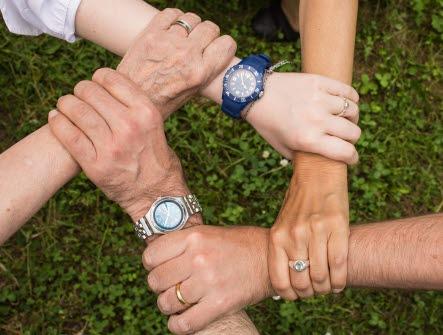 5 händer som greppar varandras handleder, formar en cirkel. På två av handlederna sitter det armbandsur i silver och blått. I bakgrunden syns grönt gräs.