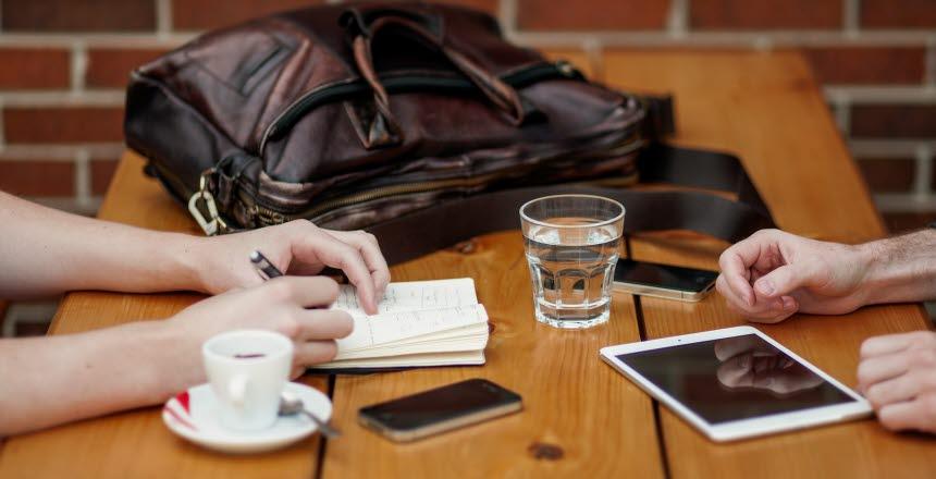 Två personer sitter vid bord och har möte, väska, vatten, glas, kaffe, mobil, telefon, anteckning, penna, hand, händer, skriva, planering, papper, ipad, padda, planera,