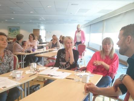 Människor som sitter i en utbildningssal kring flera mindre bord och samtalar