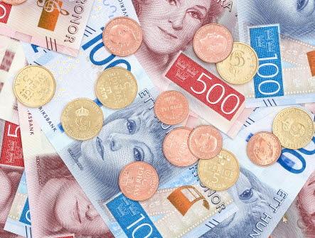 Pengar som ligger i en utspridd hög med både sedlar och mynt