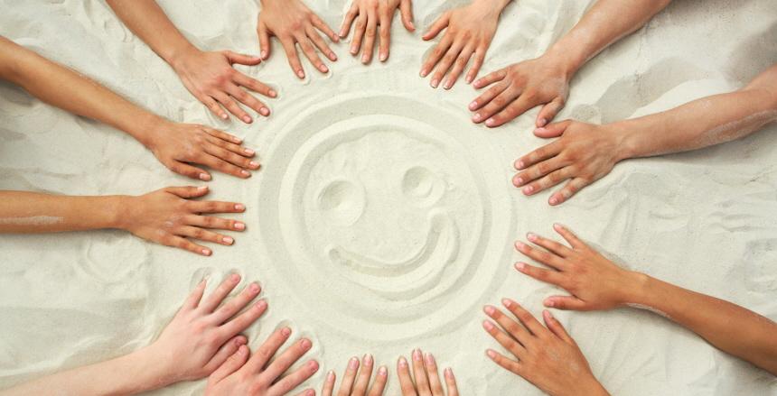händer som pekar mot glad gubbe ritad i sand