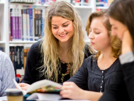 Fyra studenter på bibliotek