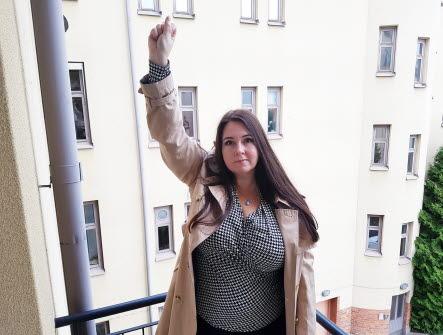 En kvinna som lyfter sin högra arm och hand med knuten näve