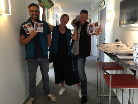Tre personer ur avdelning Blekinges styrelse ler och sträcker fram brochyrer om Vårdförbundet