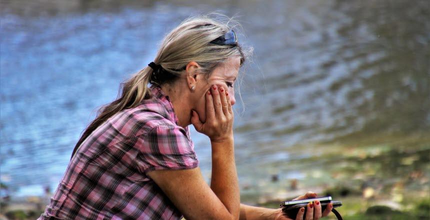 Kvinna som sitter vid en sjö och tänker