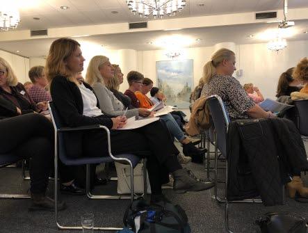 Medlemmar som sitter i biosittning i ett konferensrum.