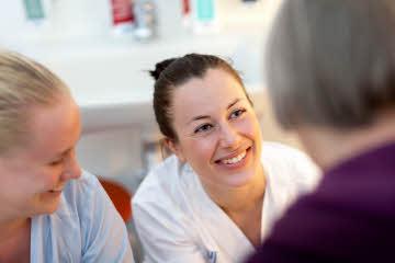 Glad sjuksköterska i vita kläder samtalar med patient