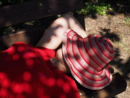 En kvinna i röd t-shirt ligger på rygg under ett träd med en röd-vit hatt över ansiktet. Det är omväxlande sol och skugga över henne.