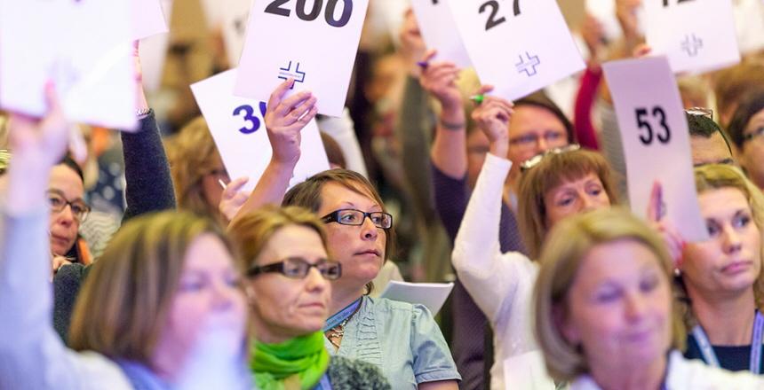 Medlemmar som håller upp röstningslappar med nummer