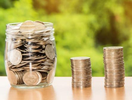 Pengar i en burk och i tre staplar