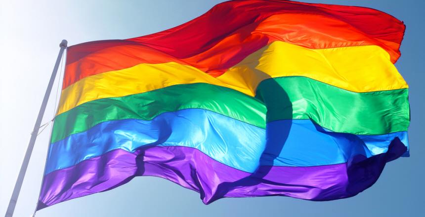 Flagga med regnbågens alla färger, mot en blå himmel.