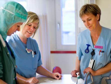Tre sjuksköterskor står och tittar neråt på något.