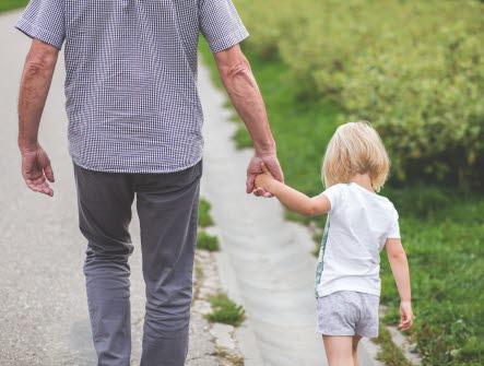 Man går på en väg med en flicka i handen. bakifrån, rygg, hand, hand i hand, flicka, man, gubbe, liten, sommar, barn, fritid, pensionär