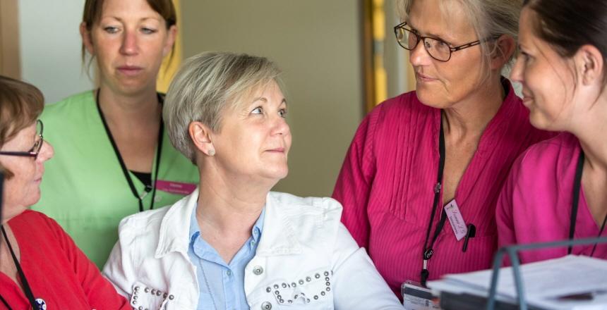 Fem kvinnor i sjukvårdskläder som pratar med varandra. En kvinna sitter i mitten och dom andra står runt om henne.