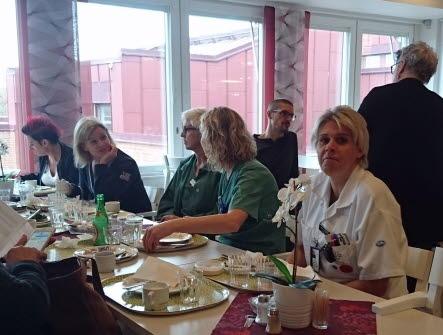En grupp kvinnor i sjukhuskläder sitter vid ett bord och samtalar och äter