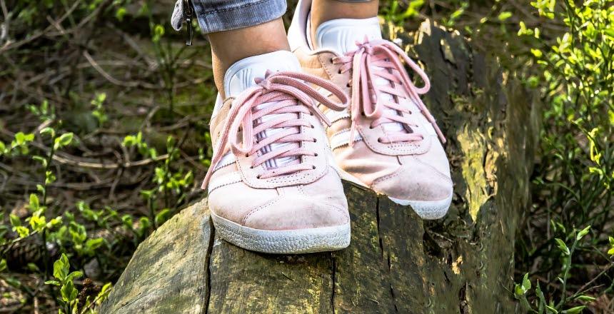 närbild på fötter med skor som går i sommarskog