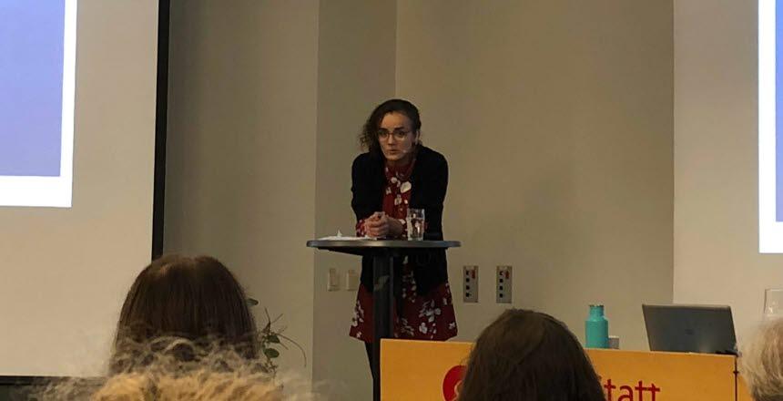 En kvinna står lutande på ett ståbord och pratar inför en publik.