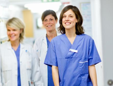 Tre kvinnor i sjukhuskläder kommer gående i en korriodor och ler