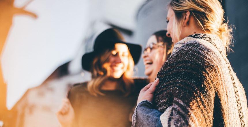 Tre tjejer som står och pratar med varandra och skrattar. En av tjejerna bär hatt, en bär poncho.