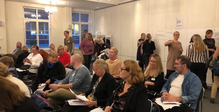 Ett konferensrum där med en massa folk. Några sitter i biosittning på stolar, andra står i små grupper och pratar med varandra.