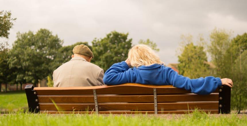 ett äldre par som sitter bredvid varandra på en bänk